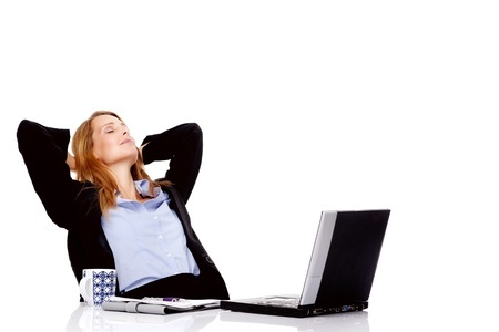 woman leaning back in a chair with a laptop open in front of her