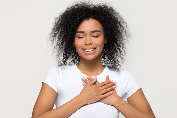 woman smiling hands on heart