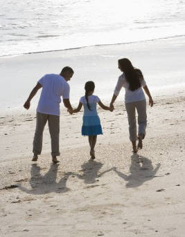 family holding hands on the beach - attachment therapy