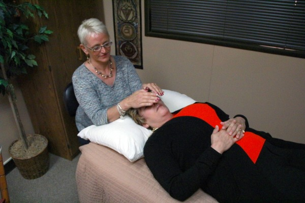 woman holding hands over prone woman's face