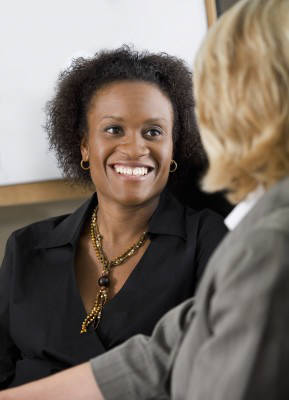 woman smiling while talking to another woman - internship