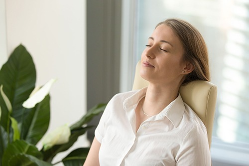 woman smiling with her head laying back against a chair headrest practicing breathwork